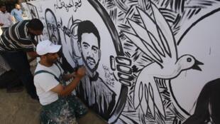 Palestinians paint a mural depicting prisoners Mahmoud Al-Sarsak (R) and Akram al-Rekhawi in Rafah, 10 June, 2012