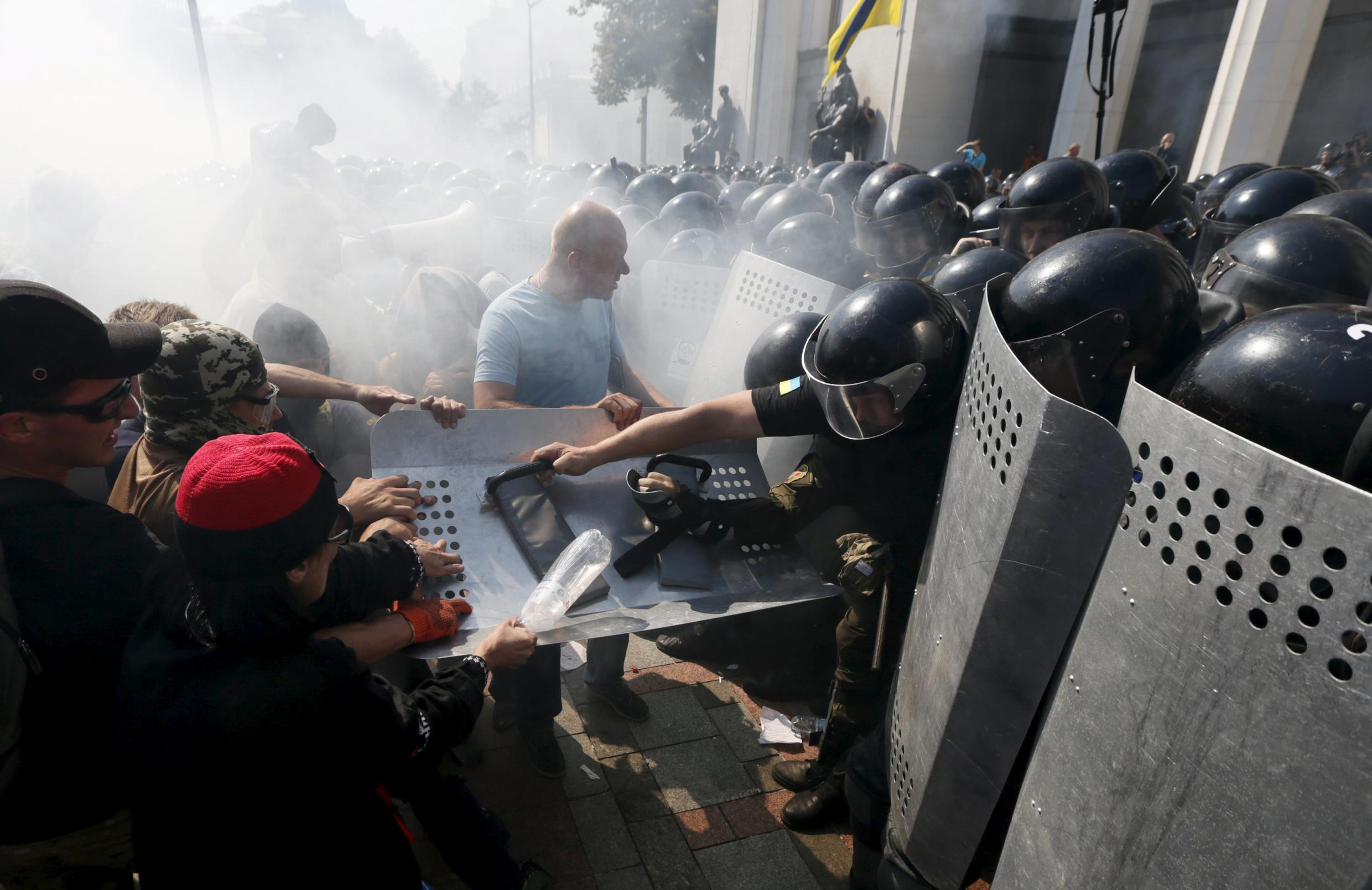 Demonstrators, who are against a constitutional amendment on decentralization, clash with police outside the parliament building in Kiev, Ukraine, August 31, 2015.