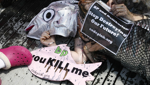 A Codepink activist  lies on the sidewalk during a staged demonstration outside BP's corporate headquarters in Houston