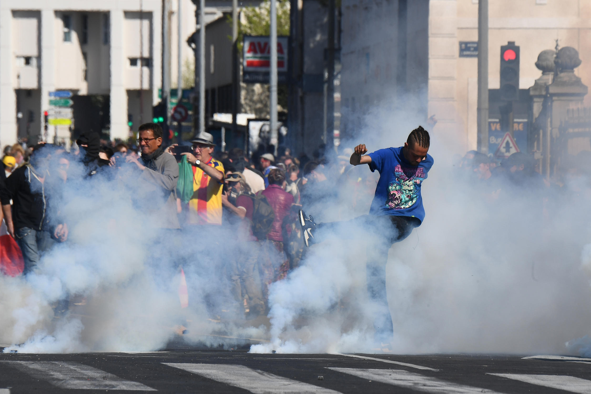 A protester kicks back a tear gas canister during clashes with police at a demonstration in Avignon southeastern France, 30 March 2019.