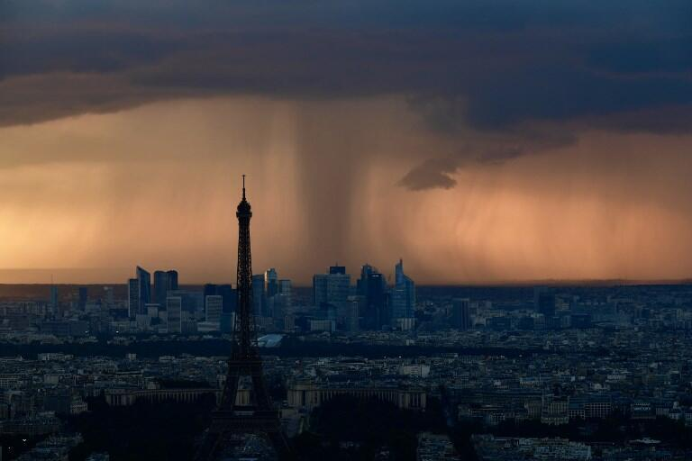The Eiffel Tower and Paris's La Défense business district under heavy clouds at sunset on Wednesday