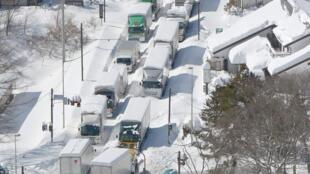 Sur une route nationale à Karuizawa, ce samedi 16 février, camions et voitures sont bloqués par d'épaisses chutes de neige.