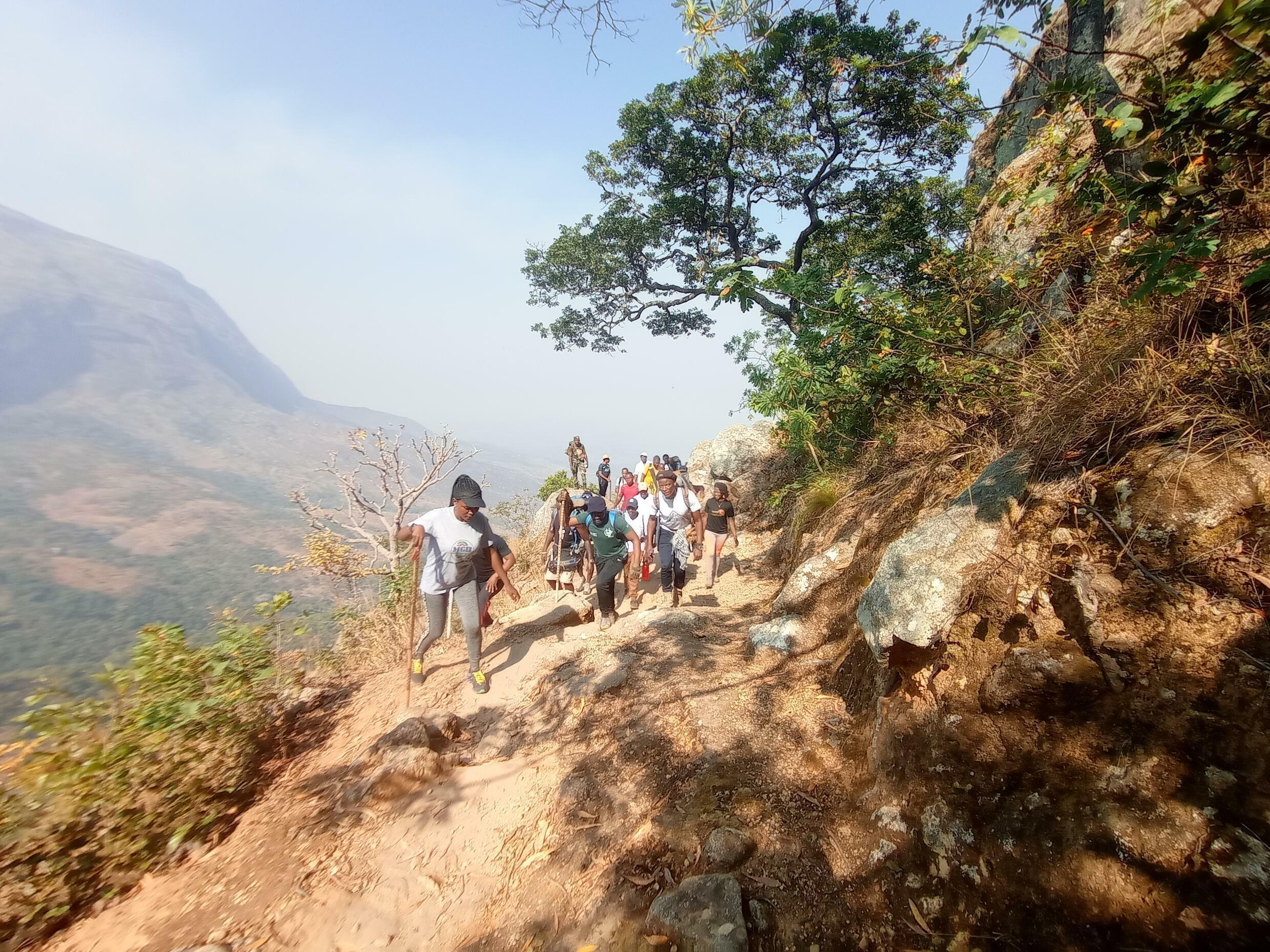 A group of Malawians hiking up Mt. Malanje with musician Lawi to call attention to conservation efforts.