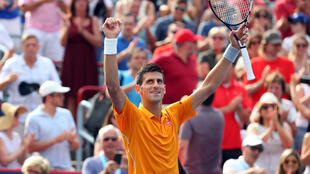Novak Djokovic of Serbia waves to the crowd after winning against Jeremy Chardy of France during the Rogers Cup
