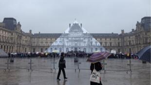 Una fotografía gigante tapa por completo la pirámide del Louvre. La instalación es del artista francés JR.