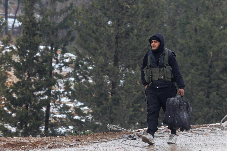 Un combattant rebelle marchant arme à la main vers les bastions de la province d'Alep restés sous contrôle des insurgés, le 22 décembre 2016.