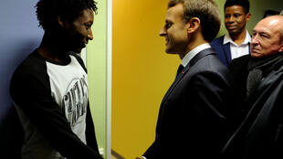 Emmanuel Macron cumprimenta o sudanês Ahmed Adam (esq.) durante visita a um centro de acolhimento de migrantes em Croisilles, nos arredores de Calais.
