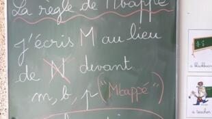 En francés, delante de las letras 'm', 'b' y 'p', se pone una 'm' y no una 'n'.