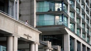 Un homme, depuis un balcon d'un immeuble près de l'Opéra de Sydney, suite à la mise en œuvre de règles plus strictes de distanciation sociale et de confinement pour limiter la propagation du coronavirus, à Sydney, en Australie, le 6 avril 2020.