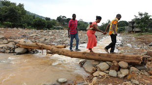 A man helps a woman cross a log bridge after the flash flood washed away a concrete bridge at Pentagon, in Freetown August 18, 2017