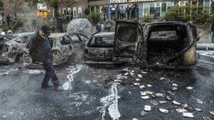 Homem passa por carros incendiados em Estocolmo, na manhã desta quinta-feira, 23 de maio