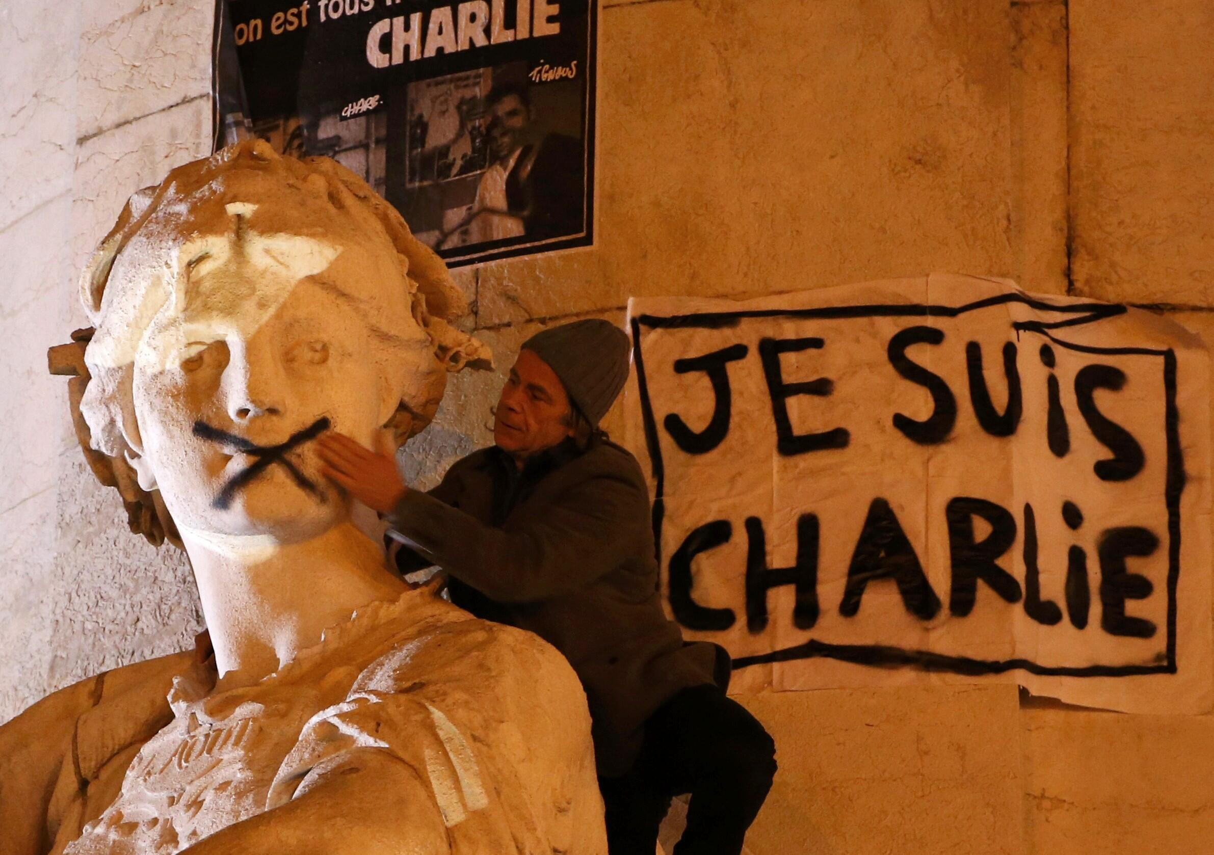 A spray-painted shut mouth of a statue in the streets of Paris, 11 January 2015.