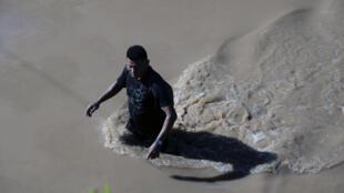 A man wades through water flooding the road from El Progreso to La Lima n Honduras