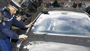 Cernée par les gendarmes et la presse, la voiture dans laquelle a pris place Dominique Strauss-Kahn, à son arrivée à la gendarmerie de Lille, le 21 février 2012.