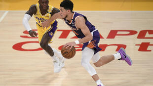 Phoenix's Devin Booker drives past Los Angeles guard Dennis Schroder in the Suns' 113-100 victory over the Lakers that clinched their NBA playoffs first-round series