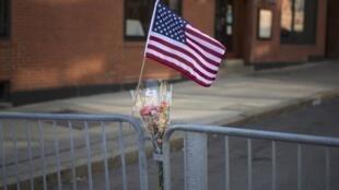 Flores e uma bandeira americana foram depositadas em uma barreira instalada pela polícia na rua Newbury, em Boston.