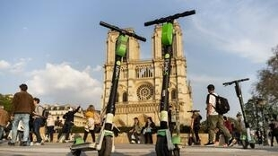 Lime-S electric scooters of US transportation company Lime are pictured in front of Notre-Dame de Paris Cathedral in Paris on April 1, 2019.