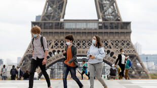 People, wearing protective masks, walk near the Eiffel Tower, September 23, 2020. REUTERS/Charles Platiau