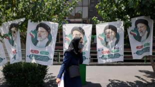 Una mujer iraní camina frente a carteles electorales, en Teherán, la capital del país, el 17 de junio de 2021
