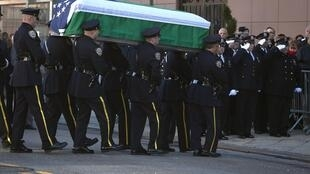Le cercueil du policier new-yorkais Rafael Ramos est transporté jusquà l'église pour la veillé mortuaire par la garde d'honneur de la police, dans le Queens, le 26 décembre.