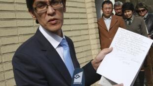 Đại diện chính phủ lâm thời Kyrgyzstan đang trưng ra lá thư từ chức viết tay của cựu tổng thống Bakiev.
