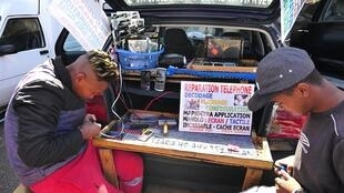 Tojo et son collaborateur réparent les téléphones dans la rue. La plage arrière du coffre de la voiture a été aménagée en établi, comme pour la trentaine d'autres réparateurs mobiles qui ont élu domicile aux abords de l'avenue de l'Indépendance.