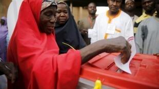 Une femme glisse un bulletin dans l'urne, ce samedi 28 mars, sur lequel est inscrit son choix pour le président, mais aussi pour son sénateur et son député.