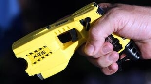 A municipal policeman in poses with the Taser X26 model