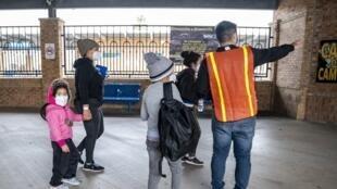 Un employé de la ville aiguille des migrants à une station de bus à Brownsville, Texas, le 2 mars 2021.