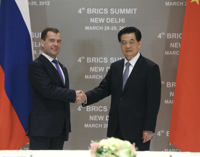 Poignée de main entre le président russe Dmitri Medvedev (G) et le président chinois Hu Jintao à la veille de l'ouverture du sommet des Brics, à New Delhi,  28 mars 2012.