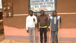 Outside the Coordinating Unit of Associations of Persons with Disabilities in Bamenda, Cameroon, (l-r) Mambi Paul Njong, Samuel Nyingcho and Ndeh Vitalis Tangeh  pose for a photo.