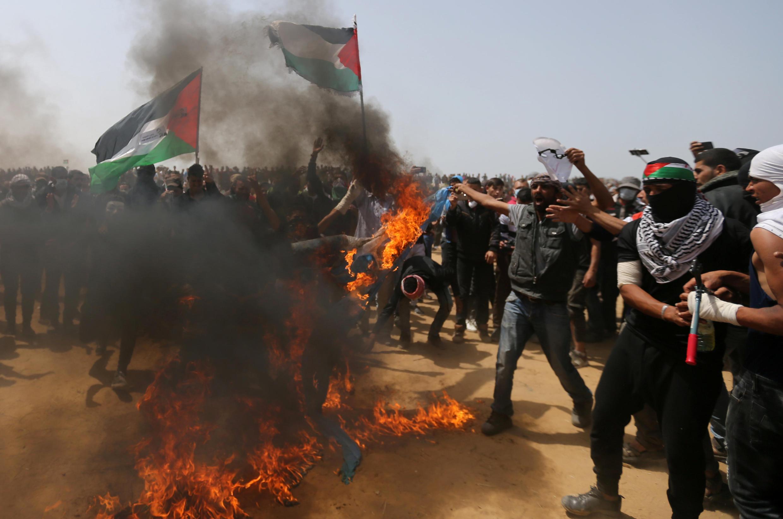 Des manifestants palestiniens brûlent un drapeau Israélien pendant le troisième vendredi de la «Grande Marche du retour» à la frontière entre Gaza et Israël, le 13 avril 2018.