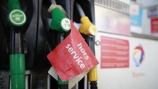 A sign reading 'out of order' at a petrol filling station near Paris
