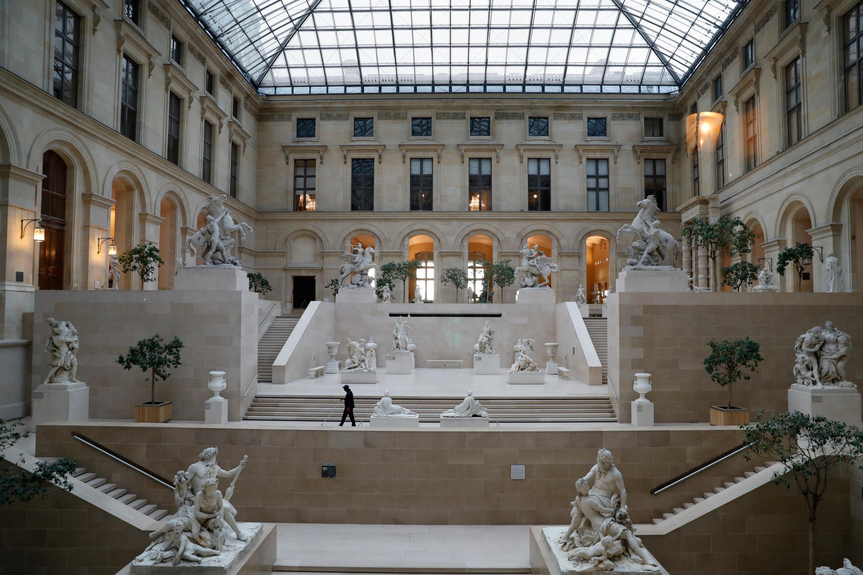 Foto del 13 de marzo de 2020, muestra a un empleado caminando en el Cour Marly en el Museo del Louvre, en París, cerrado al público en medio de las preocupaciones sobre el brote de COVID-19