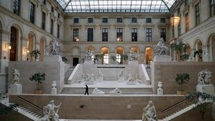 Photo from March 13, 2020, shows an employee walking in the Cour Marly at the Louvre Museum in Paris, closed to the public amid concerns about the COVID-19 outbreak.