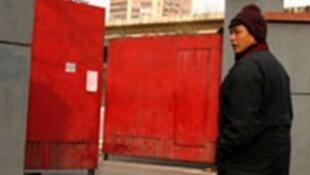"""2009年2月8日上访维权代表郑大靖站在曾经遭酷刑""""黑监狱""""门前。"""
