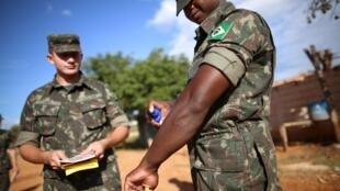 Soldados brasileiros passam repelente antes de distribuírem panfletos contra o zika