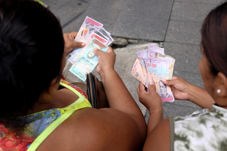 Des vénézueliennes regardent des billets de la nouvelle monnaie, le Bolivar souverain, à Caracas le 21 août 2018. La nouvelle monnaie fait partie d'une série de mesures économiques, dont l'augmentation du salaire minimum.