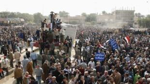 Les Irakiens investissent une place lors d'une manifestation sanglante à Kout, le 16 février 2011.
