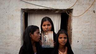Asia Bib's daughters with a portrait of their mother