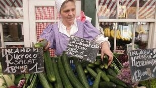 Uma comerciante vende pepinos en un mercado de Viena.