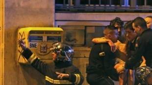 Des pompiers secourent des blessés devant la salle de concert du Bataclan, le 13 novembre 2015.