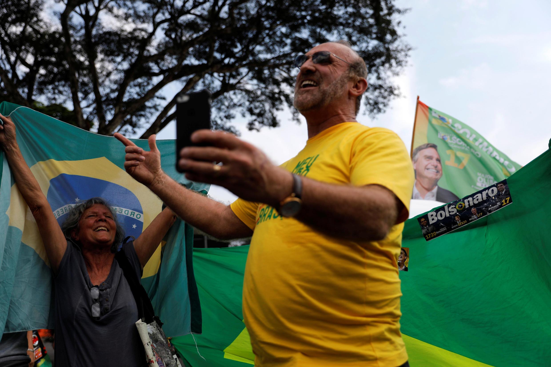 Des partisans de Jair Bolsonaro, à l'extérieur de l'aéroport Congonhas à Sao Paulo, le 29 septembre 2018, où le candidat d'extrême-droite devait s'envoler pour rentrer chez lui à Rio de Janeiro.