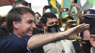 Brazil's President Jair Bolsonaro greets supporters upon arrival at Planalto Palace in Brasilia, on May 24, 2020, amid the COVID-19 coronavirus pandemic