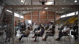 People wait to be inoculated with the AstraZeneca vaccine in Bogota. The city of eight million will be put under strict lockdown from Saturday to battle a third wave of the pandemic