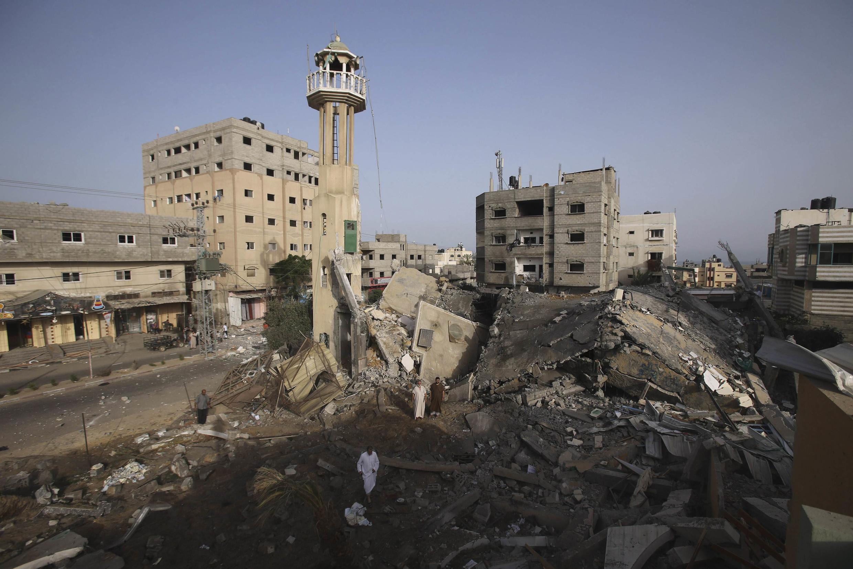 Palestinos vasculham as ruínas de uma mesquista destruída em um bombardeio israelense contra a Faixa de Gaza neste sábado (12).