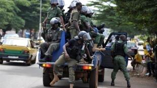 Une patrouille de police, prête à intervenir à tout moment, sillonne une rue de Conakry, le 22 octobre 2010.