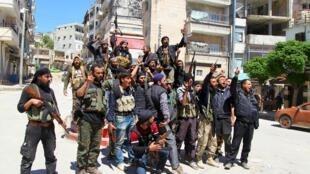 Les rebelles syriens posent devant les caméras, armes à la main, pour fêter la prise de la ville de Jisr al-Choughour, le 25 avril 2015.