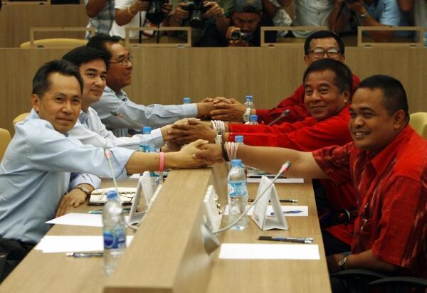 """El primer ministro tailandés, Vejjajiva, estrecha la mano del líder de los """"camisas rojas"""", Veera Musikapong."""