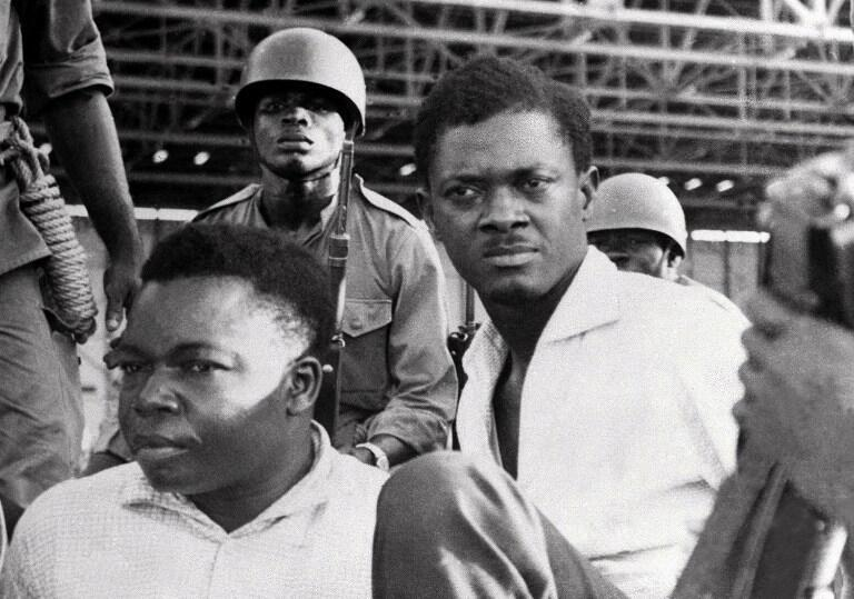 Patrice Lumumba (D), le 30 juin 1960 à Leopoldville, aux côtés du vice-président du Sénat Joseph Okito, entourés de soldats.